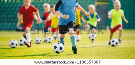 Football soccer training for kids. Children football training session. Kids running and kicking soccer balls. Young boys improving soccer skills #1100557307
