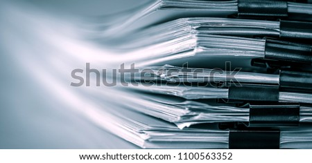 extreamely close up a report paper stacking of office working document , retro color tone #1100563352