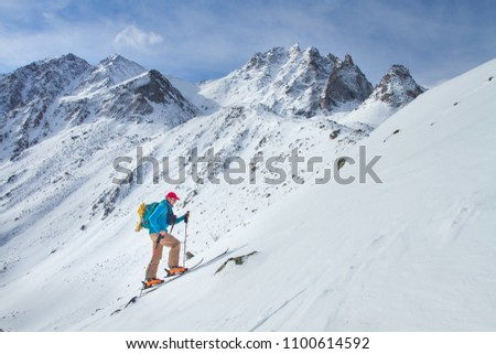 A skier walks in the mountains #1100614592