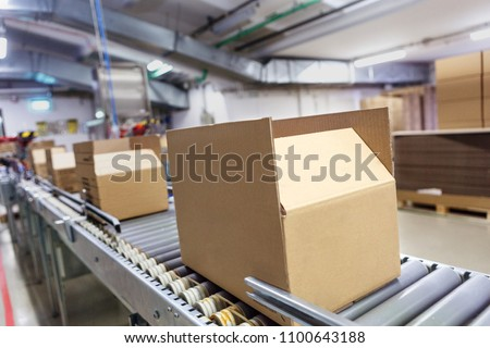 Cardboard boxes on conveyor belt. Board, package. Royalty-Free Stock Photo #1100643188