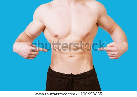 Bodybuilder man with nice abdomen pointing at this abs #1100653655