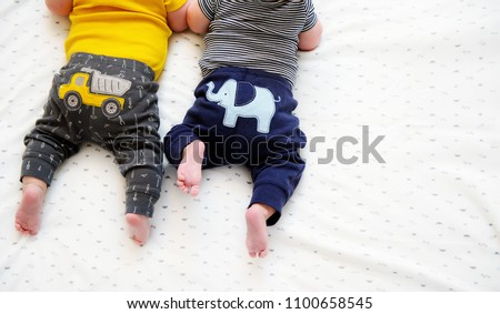 Two bottom parts and cute tiny feet of twin babies lying down. Tummy time for learning. Shot from above with free space for text. International Day for Protection of Children