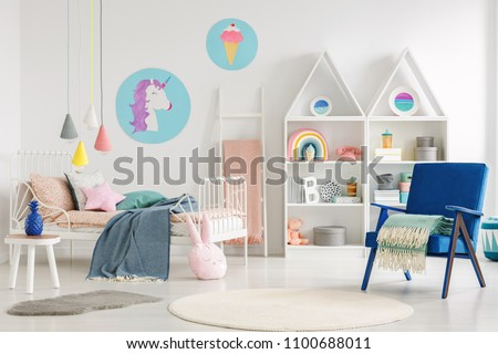 Colorful kid's bedroom interior with a unicorn and ice-cream poster, bed with sheets, rabbit pillow, shelves and blue armchair with a blanket #1100688011