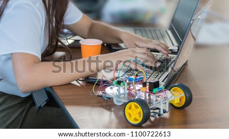 Students code a metal car robot and an electronic board. Robotics and electronics. Laboratory. Mathematics, engineering, science, technology, computer code. STEM education.  #1100722613