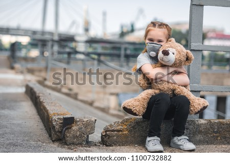 child in protective mask hugging teddy bear on street, air pollution concept #1100732882
