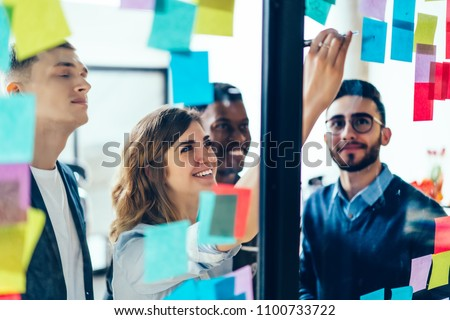 Diverse team of positive young people laughing while working together during brainstorming and standing behind glass wall with sticky colorful papers.Cheerful students learning words from stickers Royalty-Free Stock Photo #1100733722