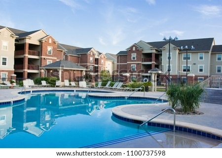 Apartment complex with beautiful swiming pool Royalty-Free Stock Photo #1100737598