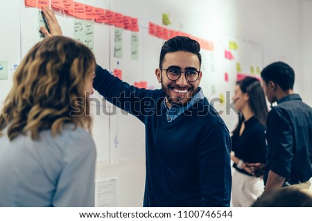 Positive young man laughing while collaborating with colleagues on creating presentation using colorful stickers for productive work in office.Male and female students having fun during workshop #1100746544