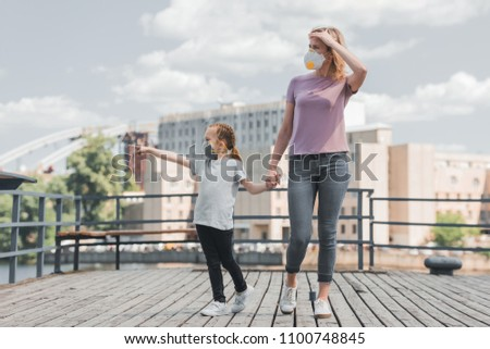 mother and daughter in protective masks holding hands on pier, air pollution concept #1100748845