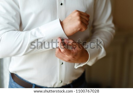 Close-up hands of man buttons cuff link on French cuffs sleeves luxury white shirt. The groom is preparing for the wedding, going to meet with the bride. Hands of wedding groom getting ready in suit #1100767028