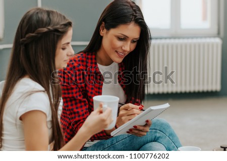 Two attractive female work colleagues having a meeting sitting together in office. #1100776202