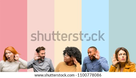 Cool group of people, woman and man holding hand near ear trying to listen to interesting news expressing communication concept and gossip #1100778086