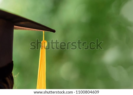 Close-up Behind photo of university graduate wears gown and black cap, yellow ribbon and green blur bokhe background.