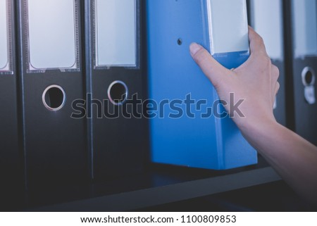 a woman officer pick a binder of document on the row of file folders and paper that nicely management system on the office's shelves and holing it with her hand Royalty-Free Stock Photo #1100809853