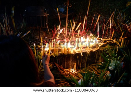 Women are lit by candles in temple at night Thailand. #1100840963