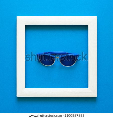 Minimalism. Masterpiece in wooden frame. Sunglasses. Top view. Flat lay. Sun protection concept.