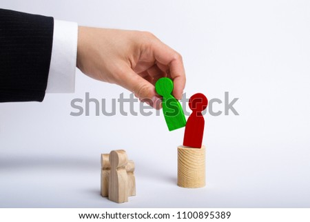 The man's hand of a businessman in a business suit holds a green figure of a man in his hand and moves the red figure from his post. The concept of firing an employee, the replacement of staff.