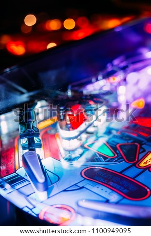 Details of a Bright and Colorful  Pinball Arcade Game Board lid with neon lights in a gaming room Royalty-Free Stock Photo #1100949095