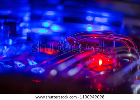 Details of a Bright and Colorful  Pinball Arcade Game Board lid with neon lights in a gaming room Royalty-Free Stock Photo #1100949098