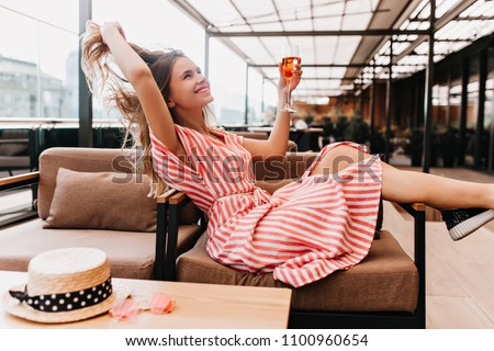 Ecstatic blonde girl playing with her hair while chilling in cafe. Inspired young woman in striped dress enjoying champagne in restaurant in summer weekend. Royalty-Free Stock Photo #1100960654