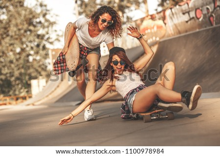 Two female friends playing with skateboard at the skate park.One girl pushing other from behind.Laughing and fun. #1100978984