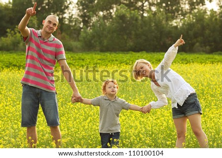 happy family having fun in the field with yellow flowers and watching up in the sky. outdoor shot #110100104