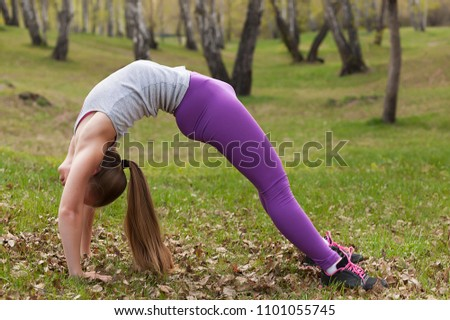 young beautiful girl doing yoga and gymnastics in the park, stretching and flexibility, pose of the bridge, yoga #1101055745