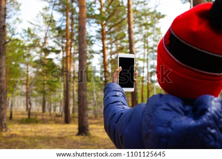 The child spends personal time in nature doing photographing the environment. Little nature Explorer taking pictures with a smart phone.