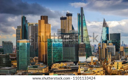 London, England - Panoramic skyline view of Bank and Canary Wharf, central London's leading financial districts with famous skyscrapers and other landmarks at golden hour sunset with blue sky #1101133424