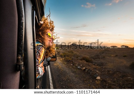 beautiful caucasian young woman travel outside the car with wind in the curly hair, motion and movement on the road discovering new places during a nice sunset, enjoy and joyful freedom concept Royalty-Free Stock Photo #1101171464