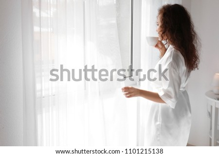Morning of beautiful African-American woman drinking coffee at home #1101215138