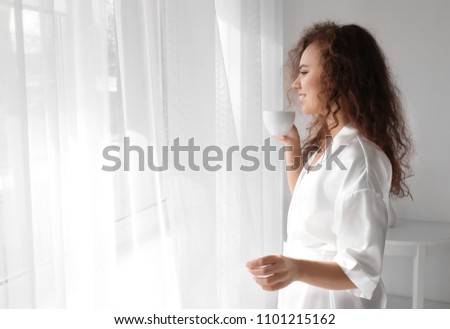 Morning of beautiful African-American woman drinking coffee at home #1101215162