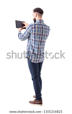 Bearded young business man pinching tablet touch screen with finger to resize. Full body isolated on white background.