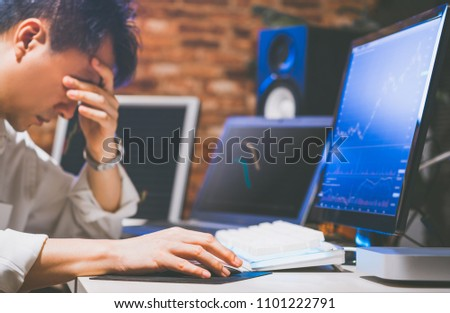 upset asian businessman at desk, depressed by working in office. feeling strain in eyes after working for long hours on computer #1101222791