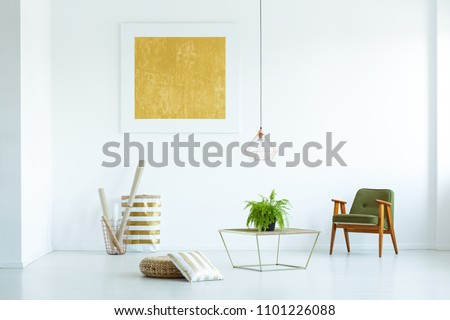 Yellow painting and green wooden armchair in white living room interior with plant on table. Real photo #1101226088