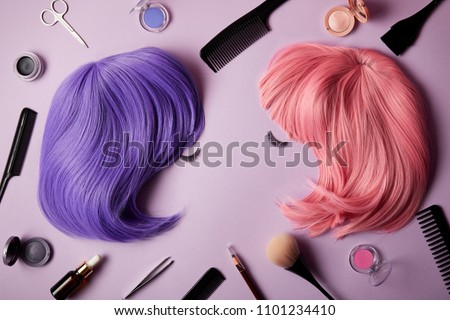 top view of pink and violet wigs, false eyelashes, makeup tools and cosmetics on purple Royalty-Free Stock Photo #1101234410
