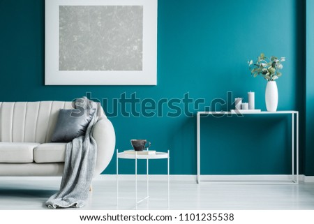 Grey painting on the green wall, white coffee table, desk, and blanket on the sofa in a modern living room interior