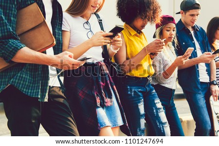 Diverse friends using their phones Royalty-Free Stock Photo #1101247694