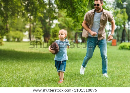 father and son running with american football ball at park #1101318896