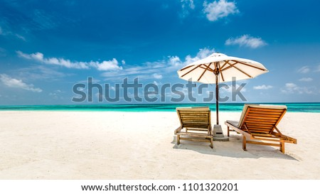 Tropical beach background as summer landscape with lounge chairs and white sand and calm sea for beach banner. Perfect beach scene - vacation and summer holiday concept. Boost up color process #1101320201