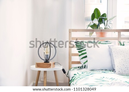 Modern and stylish bedroom with plants, design lamp and floral pattern bedding. Bright and sunny space with wooden parquet and white walls. #1101328049