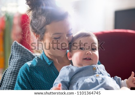 Mother is playing with her cheerful baby on the couch at home #1101364745