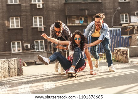 Group of friends hangout at the city street.Female sitting on skate board while friends pushing her from behind. #1101376685