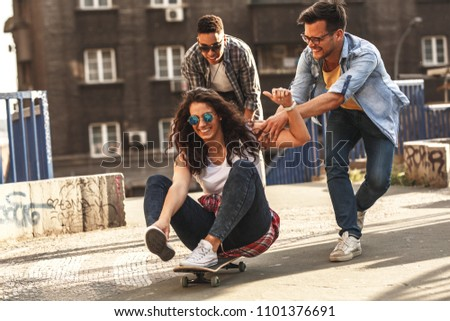 Group of friends hangout at the city street.Female sitting on skate board while friends pushing her from behind. #1101376691