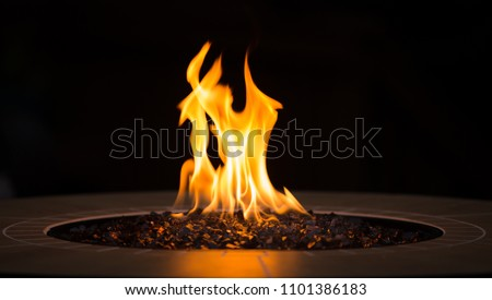Close up of an outdoor fireplace with a big yellow flame and black background #1101386183