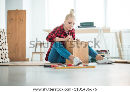 DIY concept. Young woman repairing furniture at home, sitting on the floor. Royalty-Free Stock Photo #1101436676