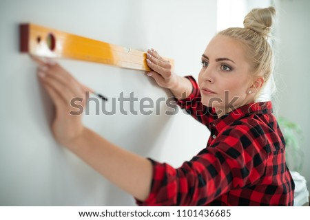 Indoor shot of young woman using leveling tool at home. Close up of face. #1101436685