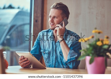 Hipster guy with a stylish haircut and beard sits at a table in a roadside cafe, talking on the phone and holds a tablet computer. #1101437396