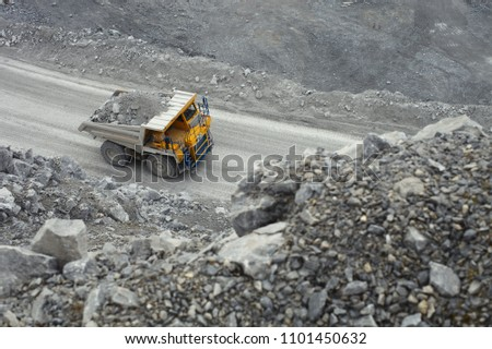Large mining dump truck loaded with rock ore rides along the road inside the quarry, top view. #1101450632