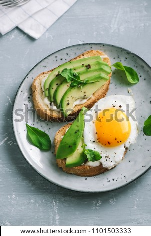 Avocado Sandwich with Fried Egg - sliced avocado and egg on toasted bread for healthy breakfast or snack, copy space. #1101503333